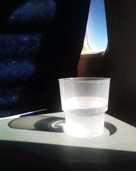 Drinking Glass Water Airplane Airport Travel Glass Half Full Optimistic StoryDrink Indoors  Close-up No People Day Journey Flying World Luxury Lifestyles Window Seat Postcards Airhostess Losangeles Zürich