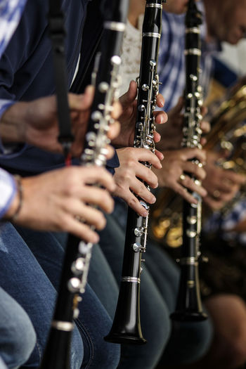 Midsection Of Musicians Playing Wind Instrument