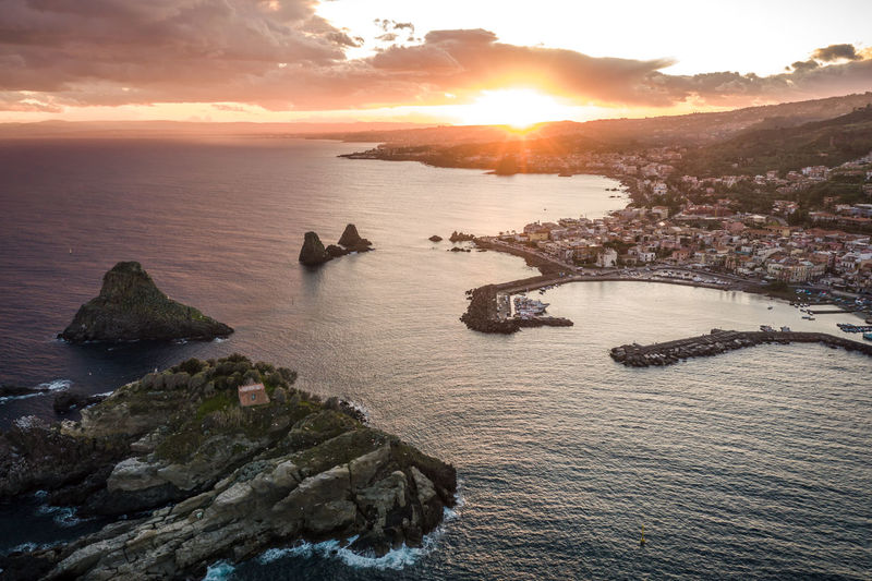 Aerial view of town by sea against sky during sunset