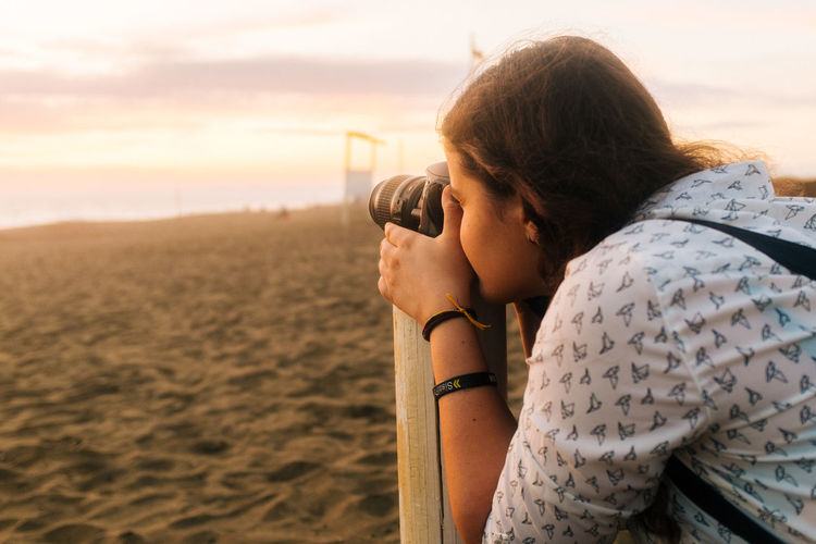 Woman photographing at beach during sunset