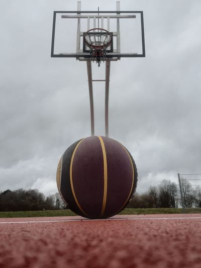 Surface level view of ball on basketball court against cloudy sky