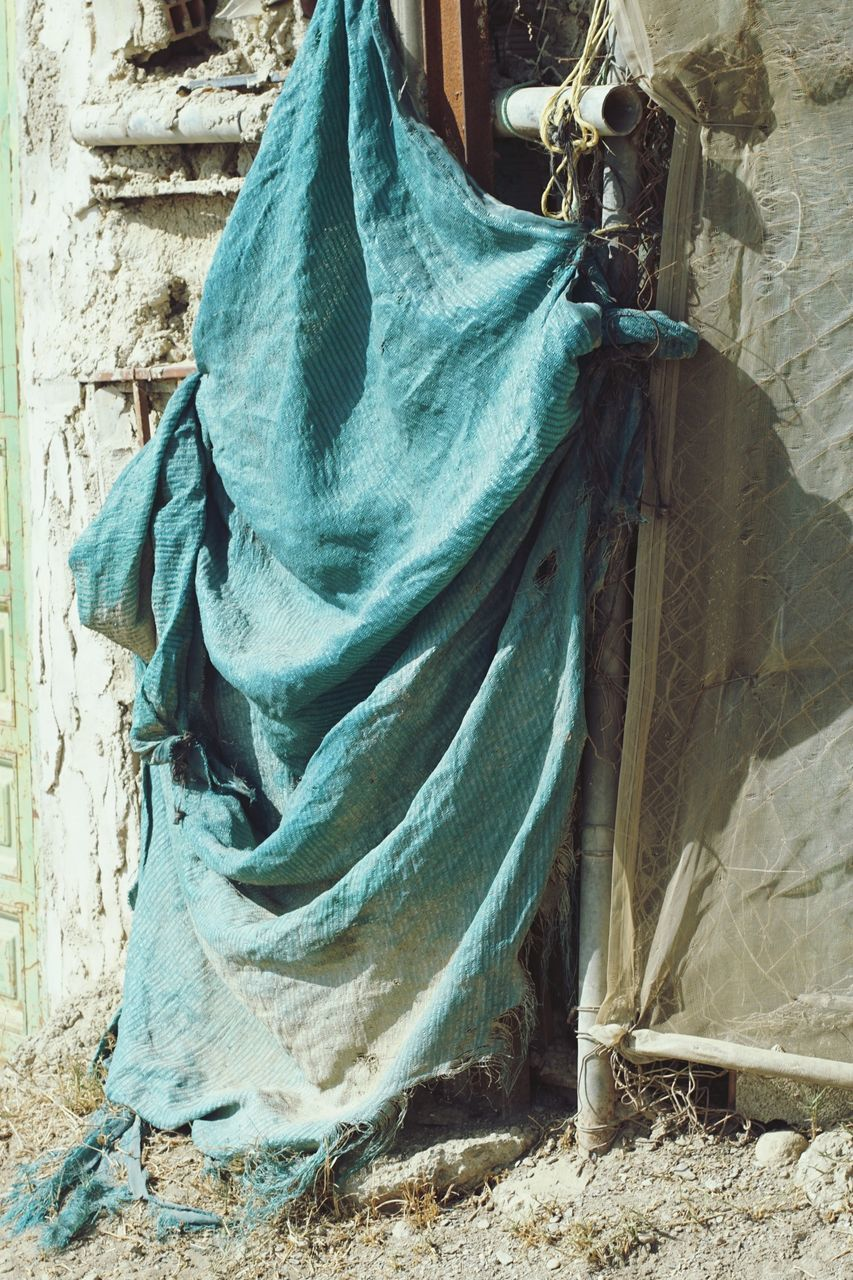 VIEW OF CLOTHES HANGING ON WALL WITH SHADOW