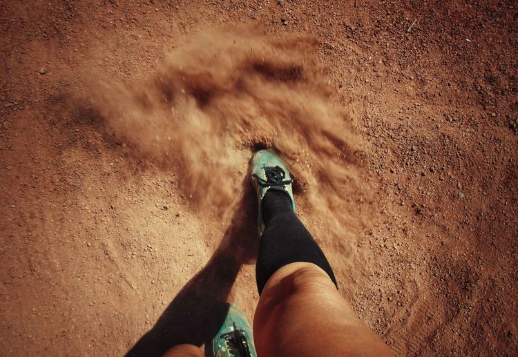 Low section of woman running on baseball field