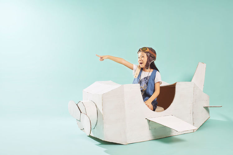 Smiling girl sitting in toy airplane over blue background