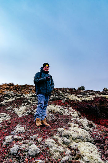Blue Casual Clothing Clear Sky Copy Space Front View Full Length Iceland Island Landscape Leisure Activity Lifestyles Looking At Camera Nature Person Rear View Rock - Object Sky Standing Tranquility Young Adult