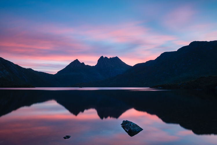 Scenic view of lake by mountains against romantic sky