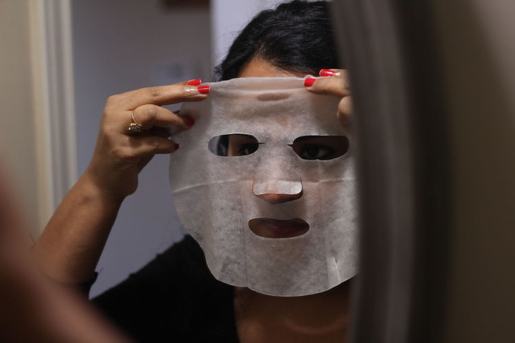 Close-up of woman applying with facial mask