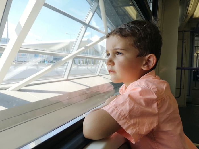 Portrait of boy looking away while standing by railing