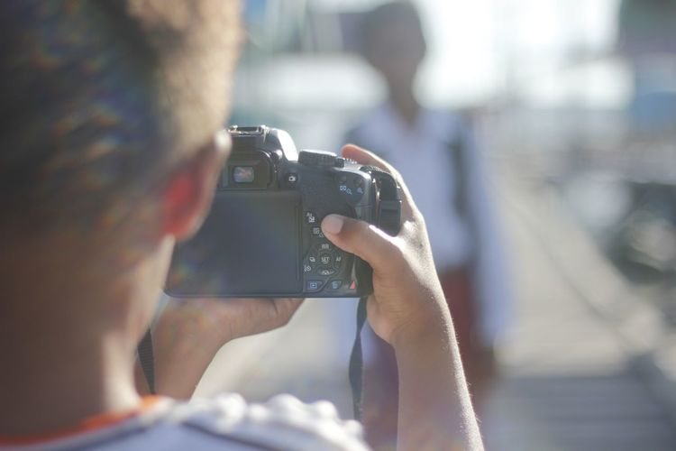 Close-up of man photographing camera on mobile phone