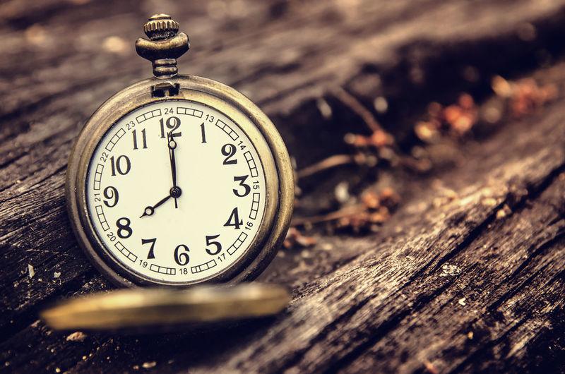Close-up of pocket clock on wood