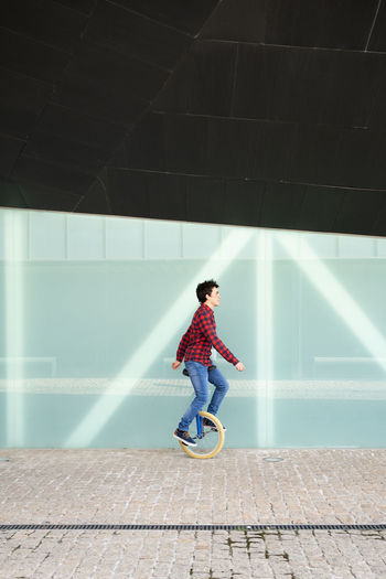 Full length of boy on footpath against wall