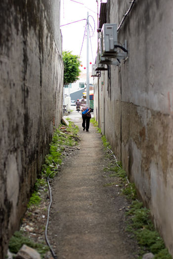 An elderly lady walks hunched along a city alleyway in to the distance. Alley Alleyway Architecture Building Exterior Built Structure City Day Direction Distance Elderly Forward Going Home Hunched Narrow Old Lady One Person Outdoors Path Pathway Real People The Way Forward Walking Walking Around