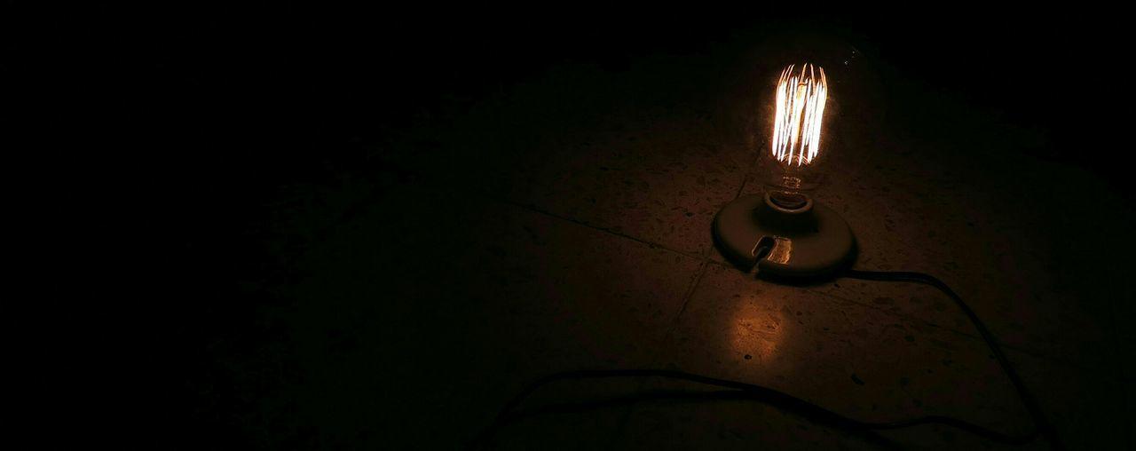 Close-up of illuminated lamp over black background