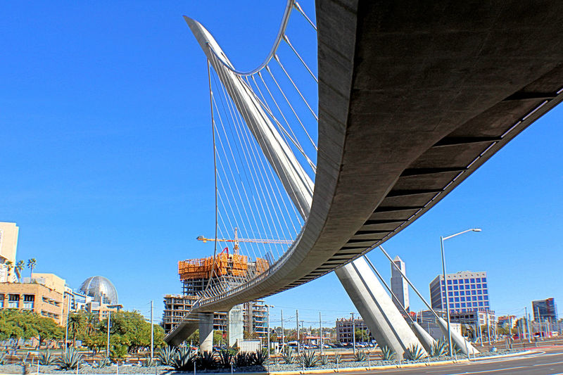 Low angle view of bridge against buildings in city