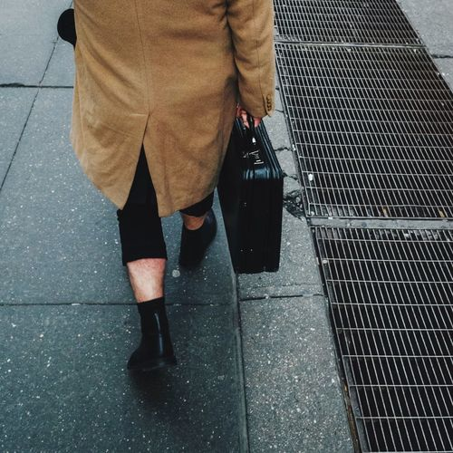 Low section of person walking with suitcase walking on footpath