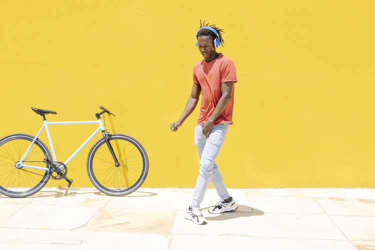 Full length of young man with bicycle standing against yellow wall