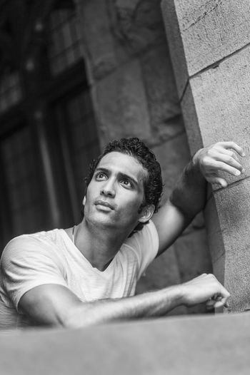 Portrait of young man standing by rock window, looking up.