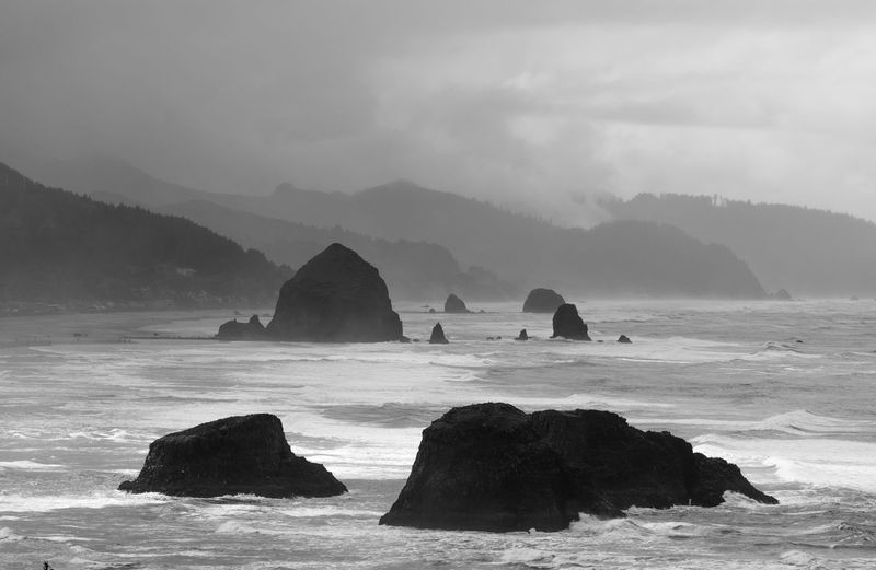 Stack Rocks In Sea Against Cloudy Sky