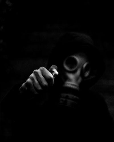 Close-up portrait of man holding cigarette against black background
