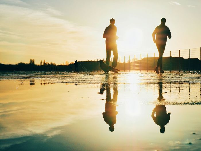 Reflection of people in puddle while jogging during sunset