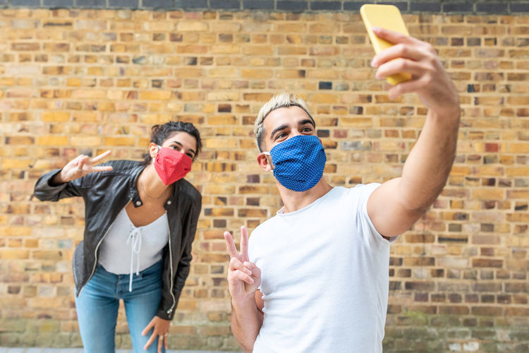 Friends wearing mask doing selfie against wall outdoors