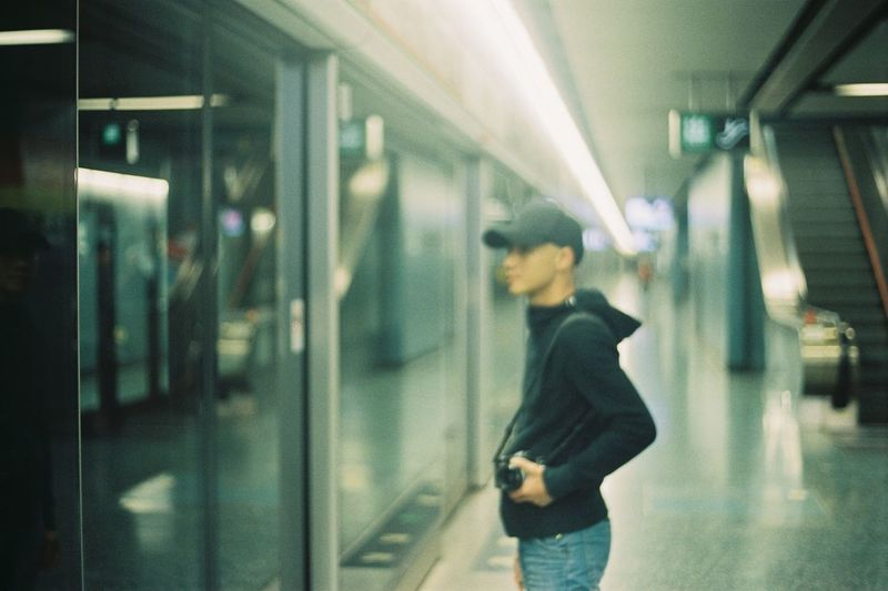 Side view of woman standing at subway station