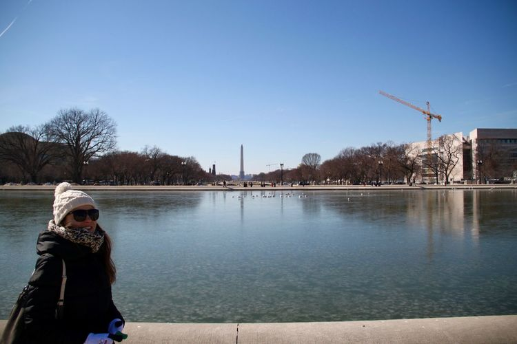 Portrait of woman standing against washington monument during sunny day
