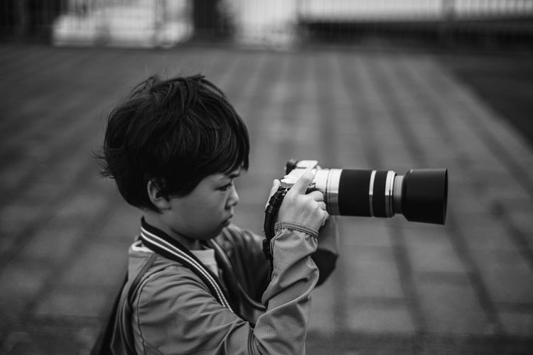 Side view of boy photographing while standing outdoors
