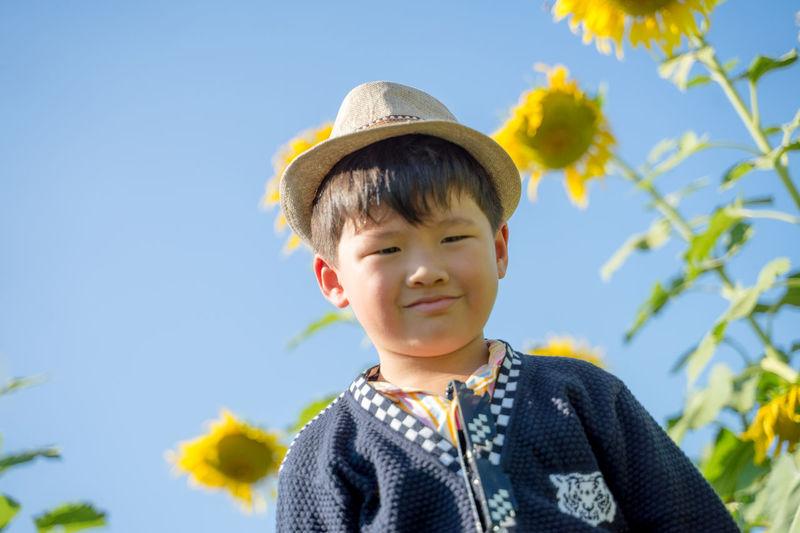 Portrait of cute boy smiling against sky