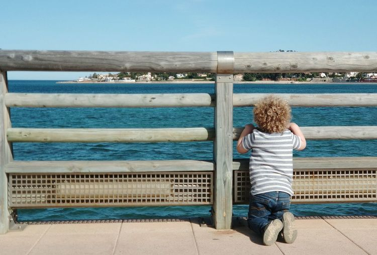 Rear view of boy looking at sea through wooden railing