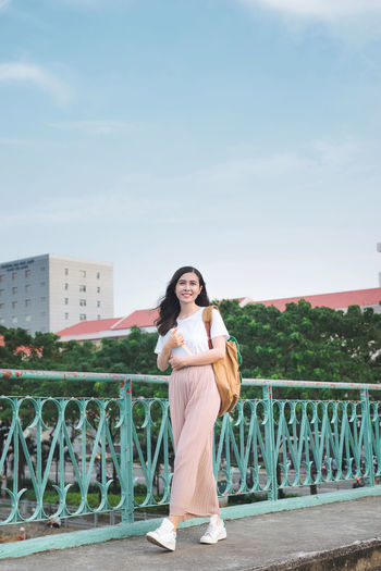 Full length of asian girl walking on a bridge with city view with a book in her hand