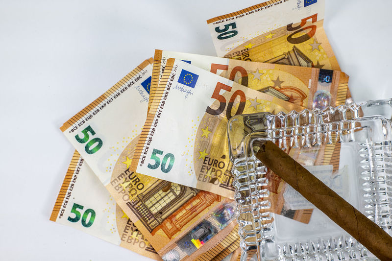 Close-up of banknotes with cigar over white background