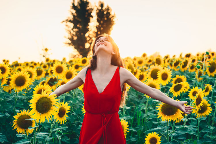Low angle view of woman standing on sunflower field against sky
