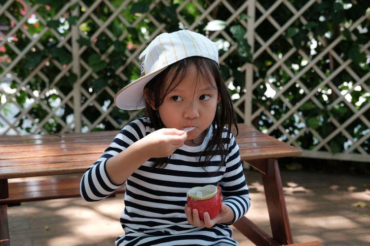 Cute Girl Eating Ice Cream Against Fence