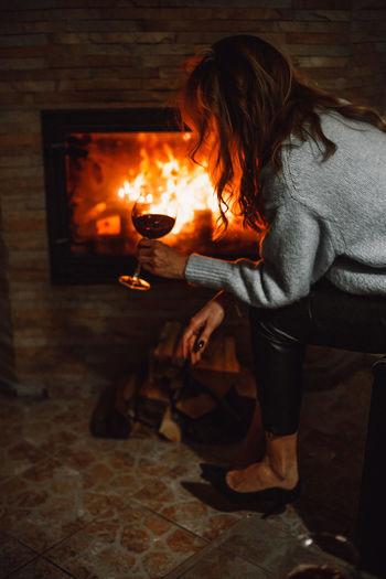 Midsection of woman with fire sitting on wooden floor