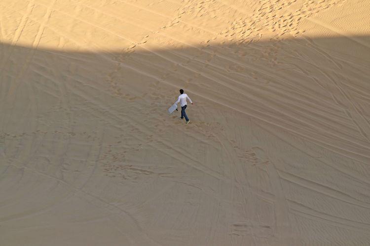 Aerial view of man walking on sand dune
