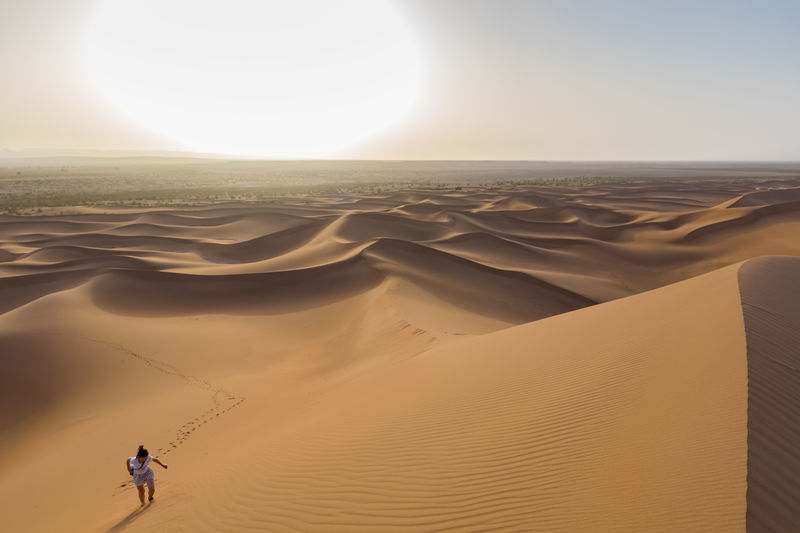 High Angle View Of Young Woman Walking At Desert Against Sky During Sunset
