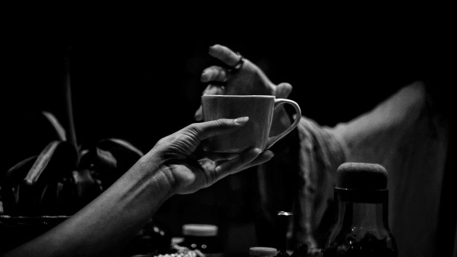 Close-up of hand holding coffee cup in darkroom