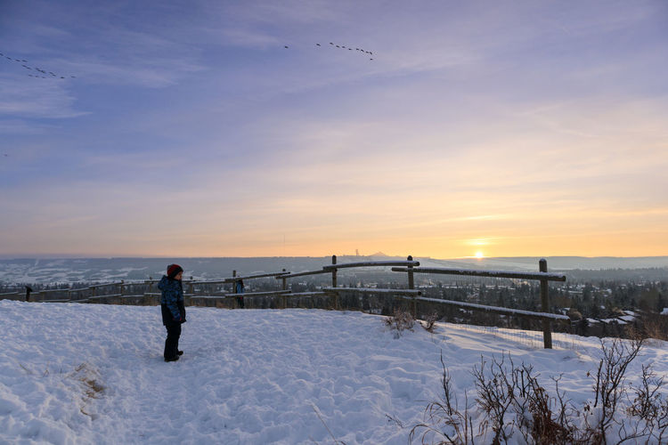 Man standing on snow covered land against sky during sunset