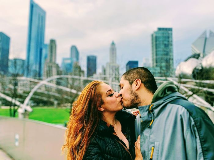 Couple kissing against cityscape in background