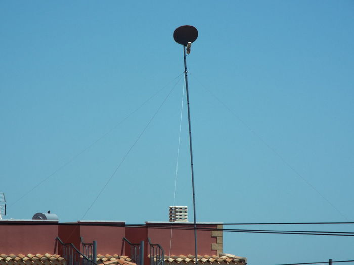 Low angle view of satellite dish and cable over buildings against blue sky