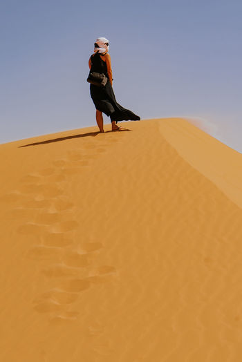 Low angle view of woman standing on sand dune with black dress and white turban