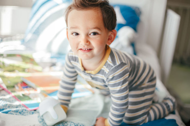 Cute adorable caucasian kid boy sitting on bed drinking milk from kids bottle. healthy eating