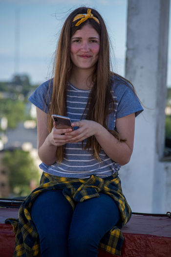 Portrait Of Smiling Young Woman Using Mobile Phone While Sitting On Retaining Wall