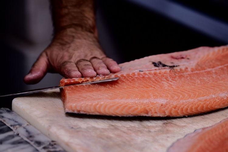 Close-up of man cutting fish on cutting board