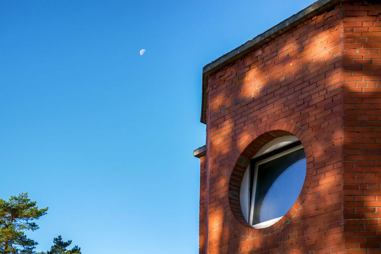 Round circle window on red brick wall building over clear blue sky with moon in morning Architecture Blue Brick Brick Wall Building Building Exterior Built Structure City Clear Sky Copy Space Day Low Angle View Moon Nature No People Outdoors Sky Sunlight Wall Window