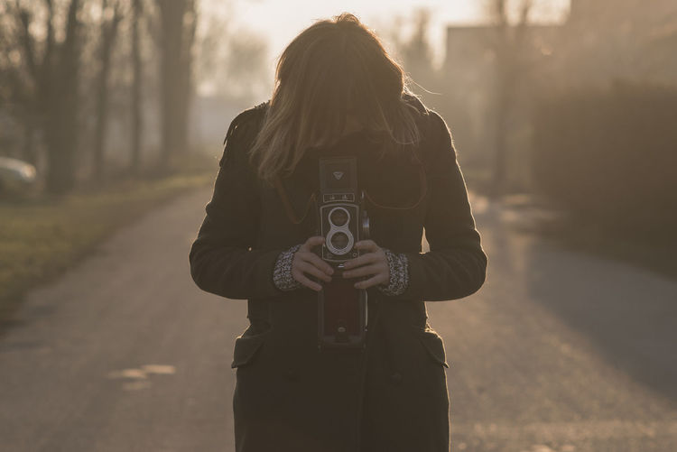 Young Woman Photographing Through Camera On Road