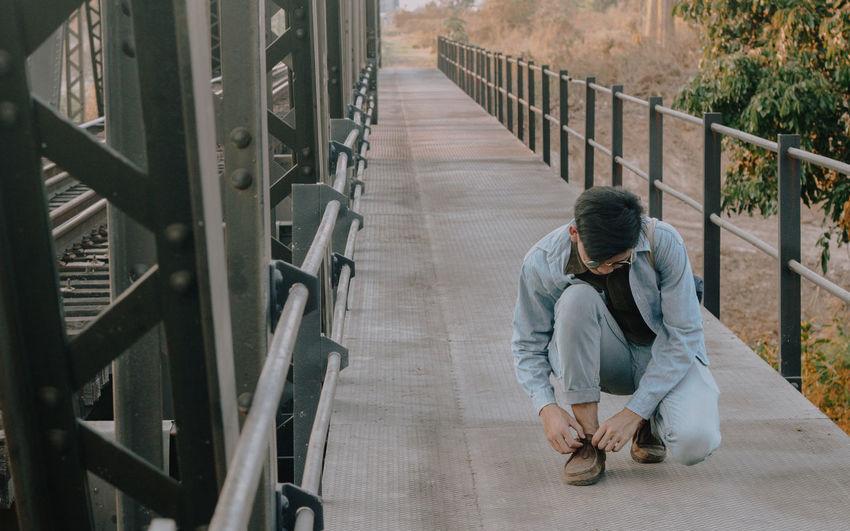 Full length of young man tying shoelace on bridge