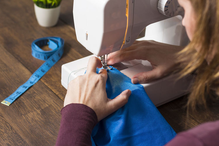Midsection of woman sewing textile on table