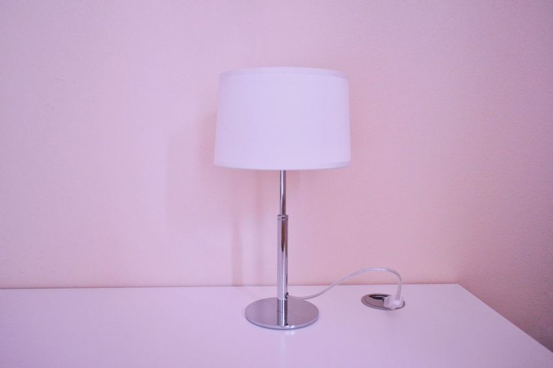 Lamp on table by wall